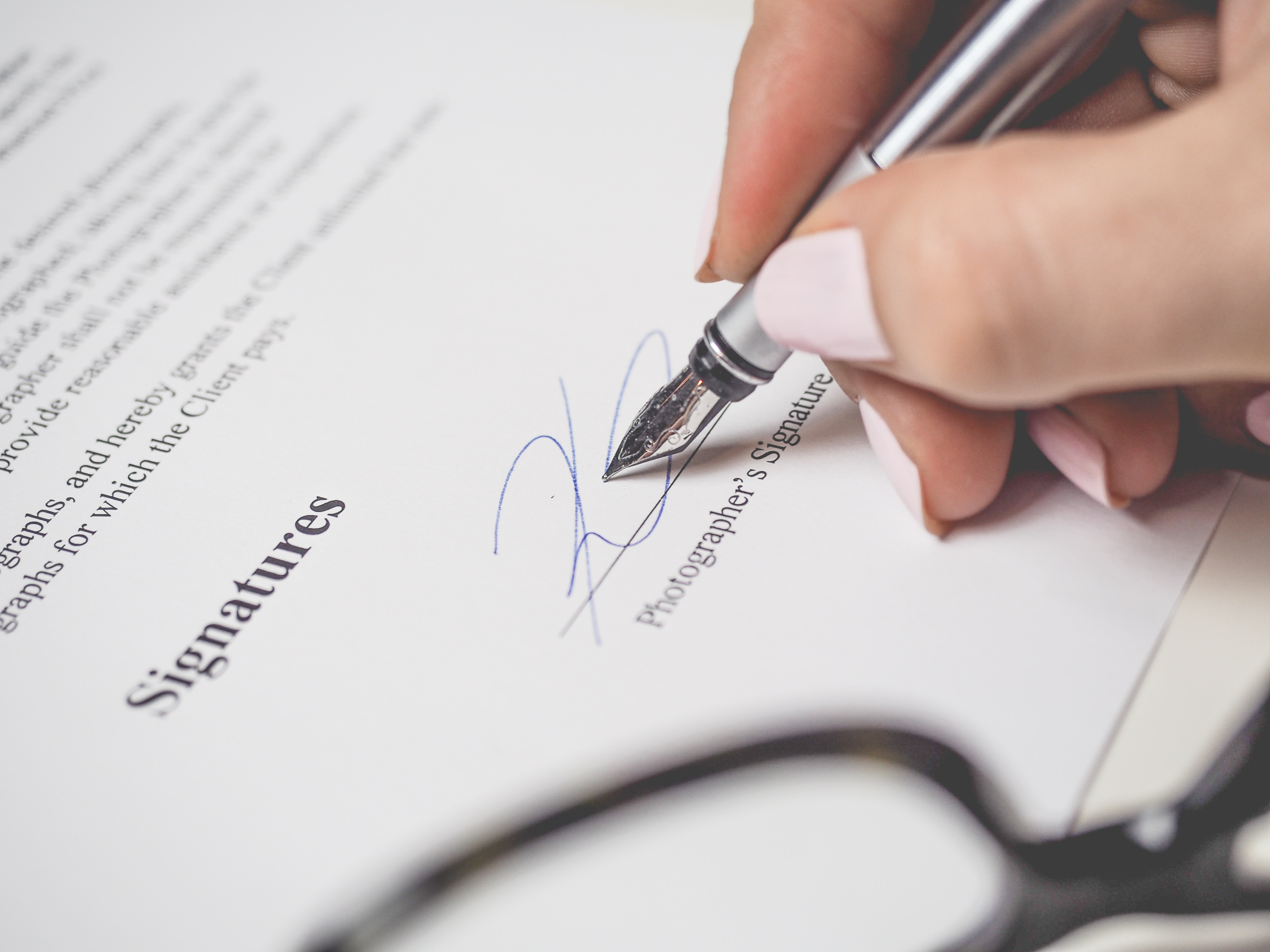 person-holding-silver-pen-signing-photographers-signature-175045
